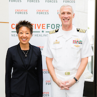 A man in military clothing is standing next to a woman smiling and posing for a picture in front of a Creative Forces sign.