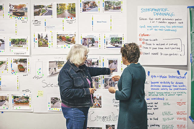 Two woman look at a wall covered with photos and ideas involving the redesign of a town's Main Street