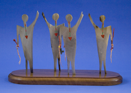 metal sculpture of four dancers with ceremonial pipes and arrow-shaped necklaces