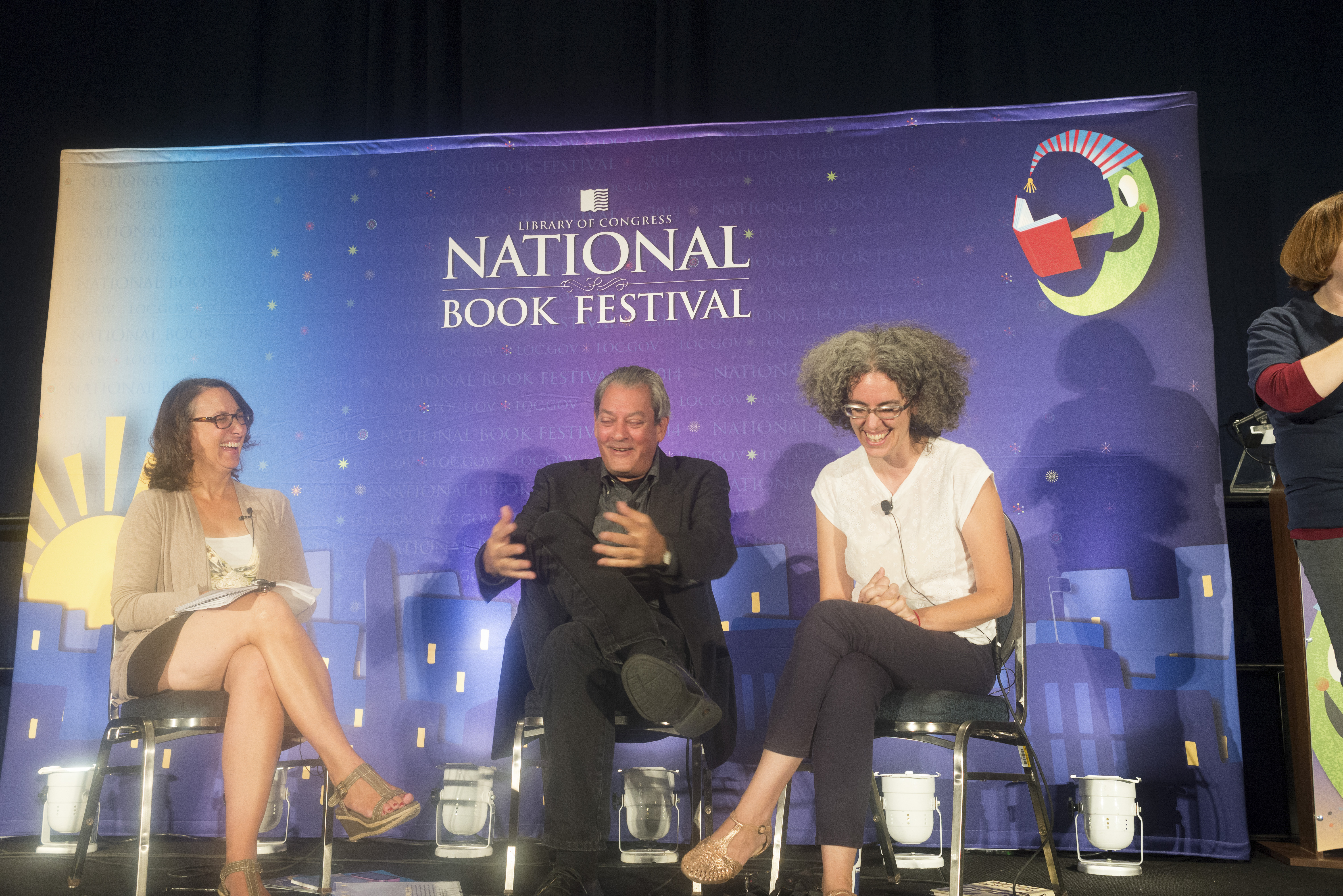 NEA Literature Director on stage smiling and laughing with NEA Creative Writing Fellow Paul Auster and NEA Literature Translation Fellow Natasha Wimmer.