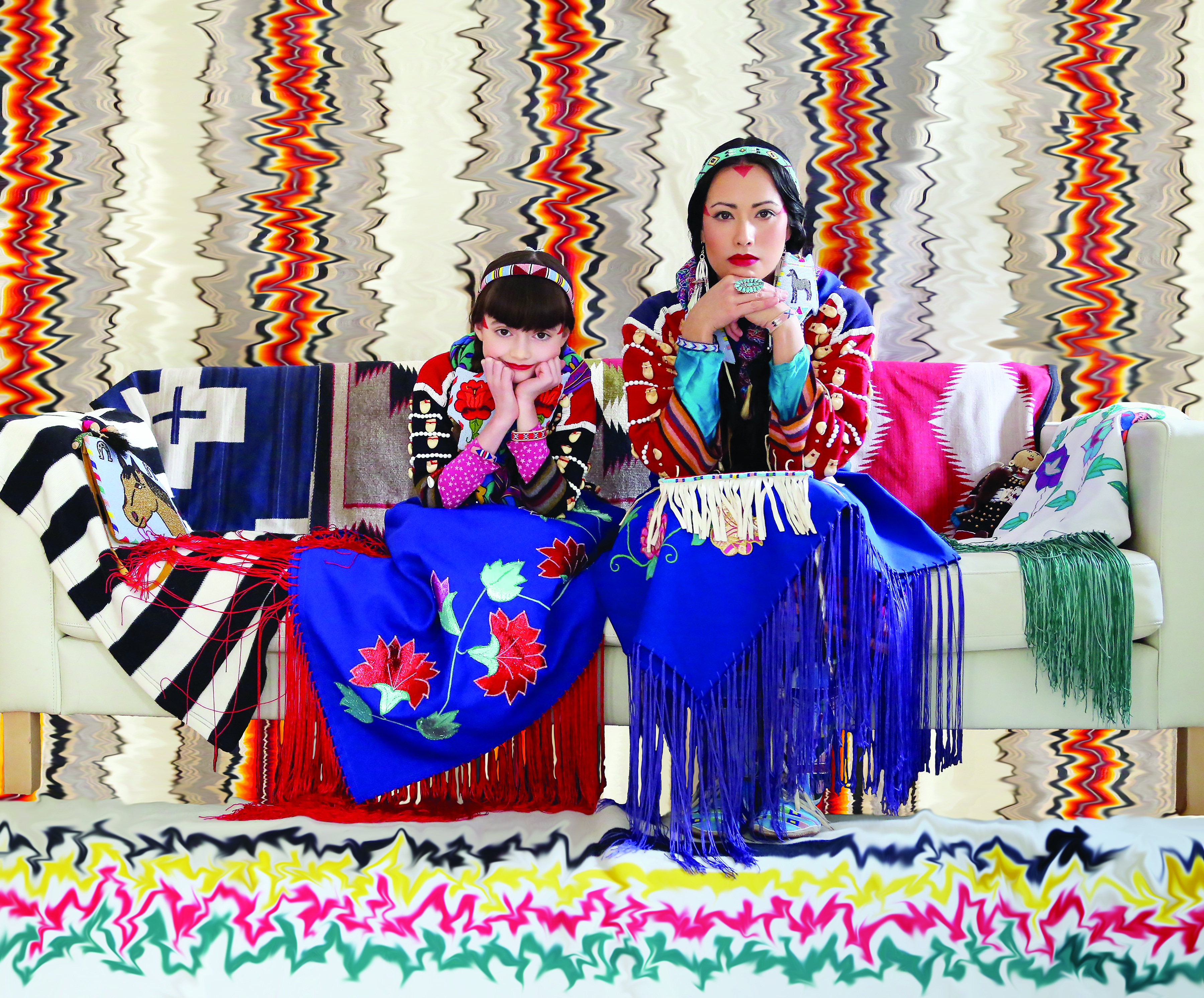 Woman and young girl dressed in Native garb sitting on a couch before a background of dizzying patterns.