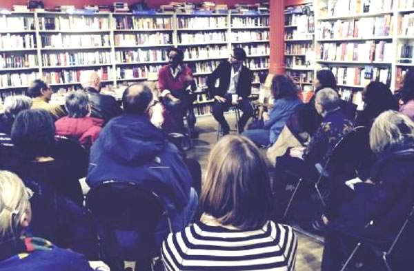 Two men facing an audience answering questions at a bookstore gathering