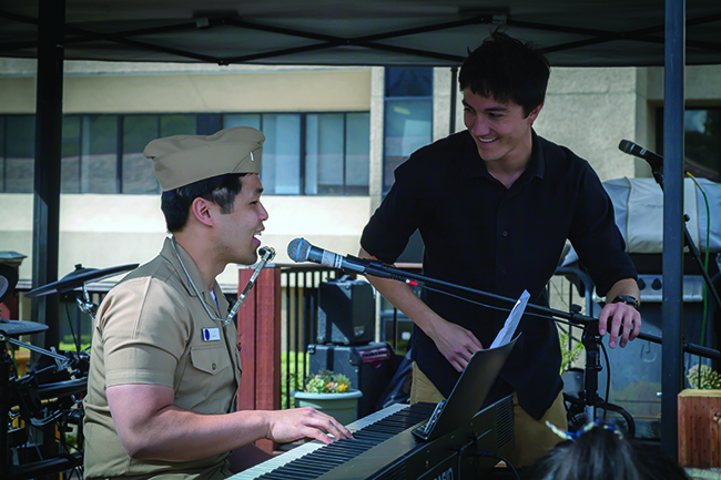 A man in brown Navy uniform plays the piano and wears a harmonica on a neckstrap while another man looks on