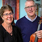 A man and a woman look towards the camera. The man hold a violin in his hand, a piano in the background.
