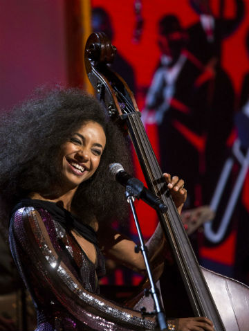 female bass player smiling and performing