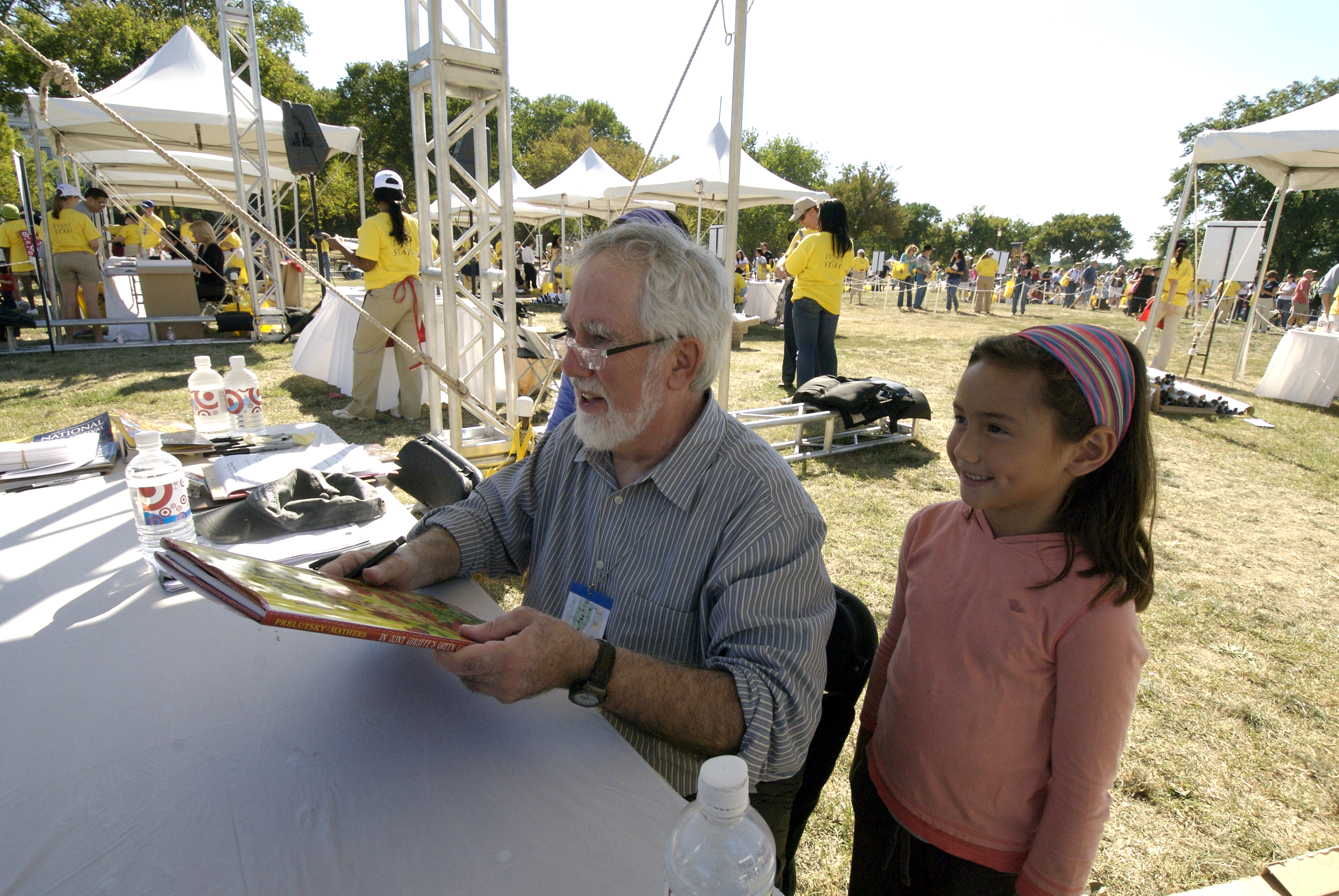 Jack Prelutsky standing next to a little girl while holding a book, smiling, and posing for a picture.