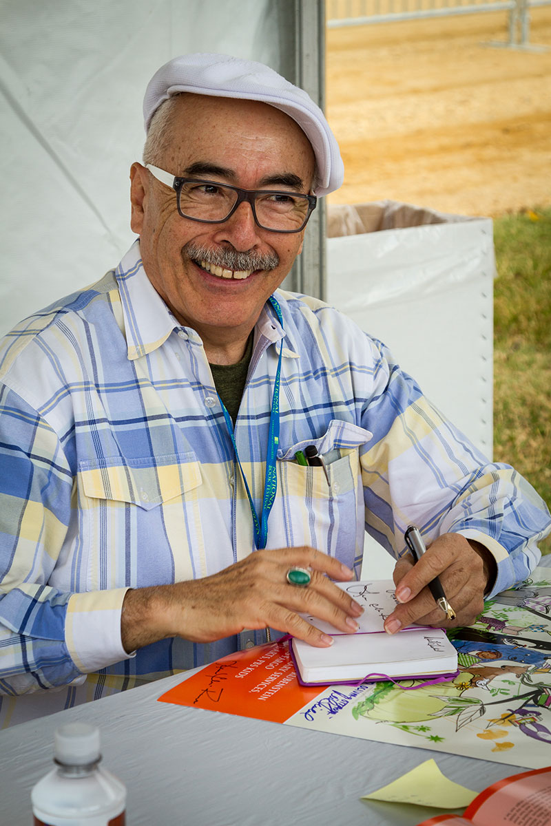 Juan Felipe Herrera sitting down at a table with a pen in his hand and looking up smiling.