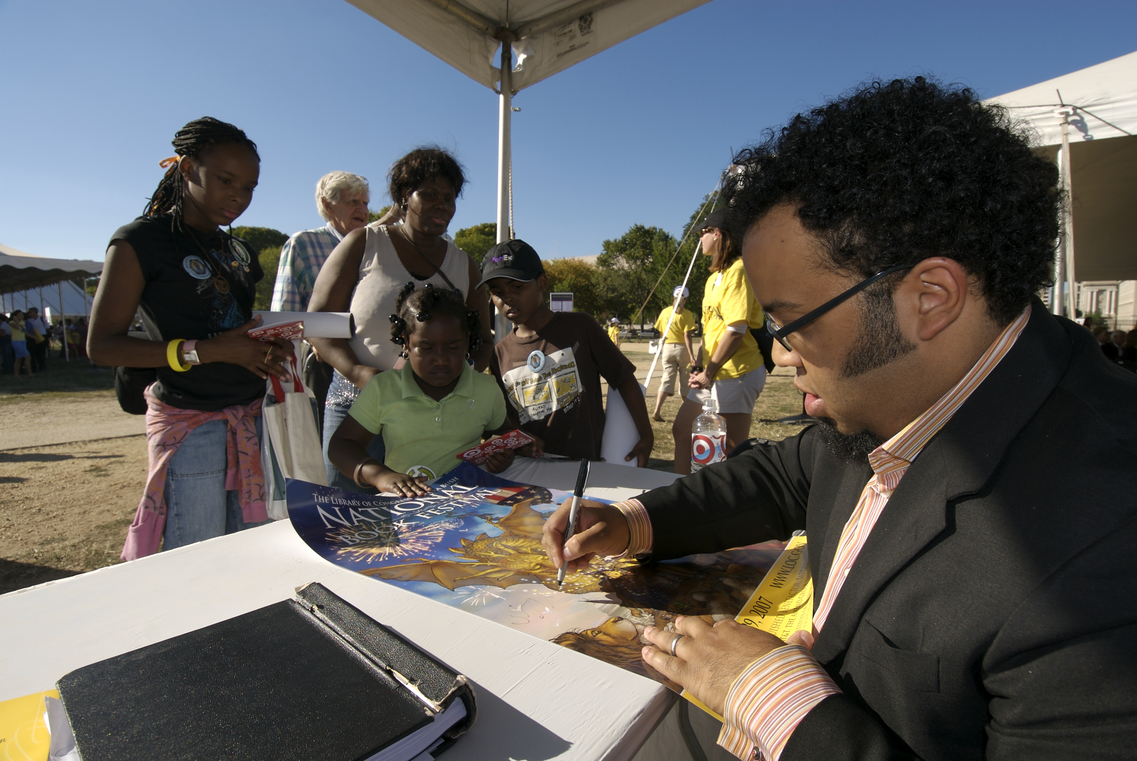 Kevin Young signing a poster with kids standing around him.