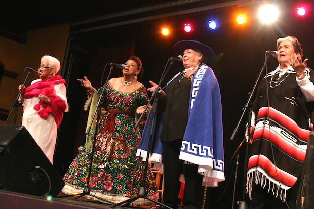 Four women dressed in Maexican attire stand before microphones on a stage.
