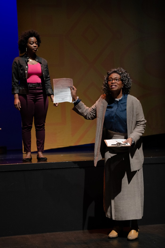 An actress asks a young audience whether anyone needs a voter registration card