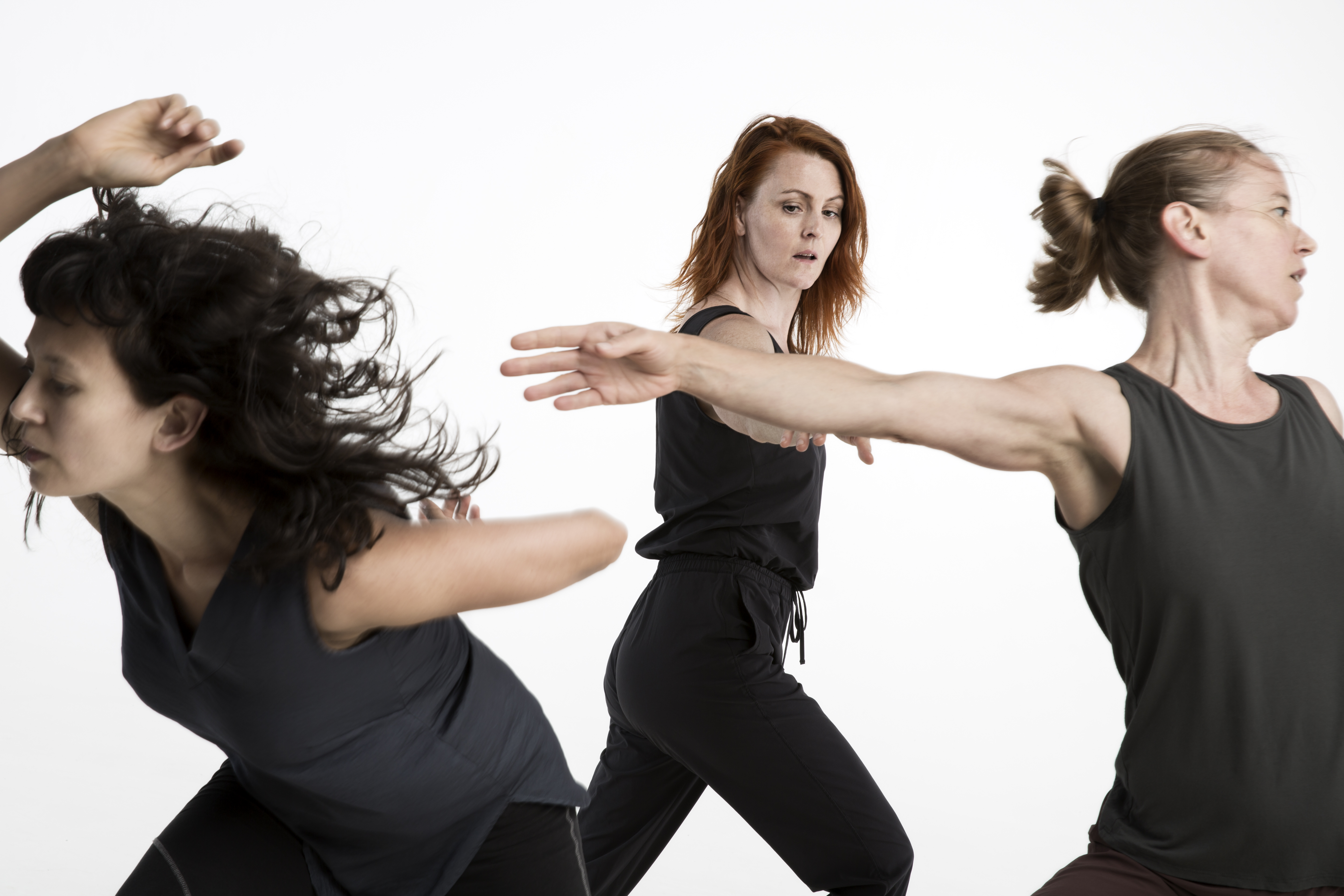 Three women wearing black dancing in different directions.