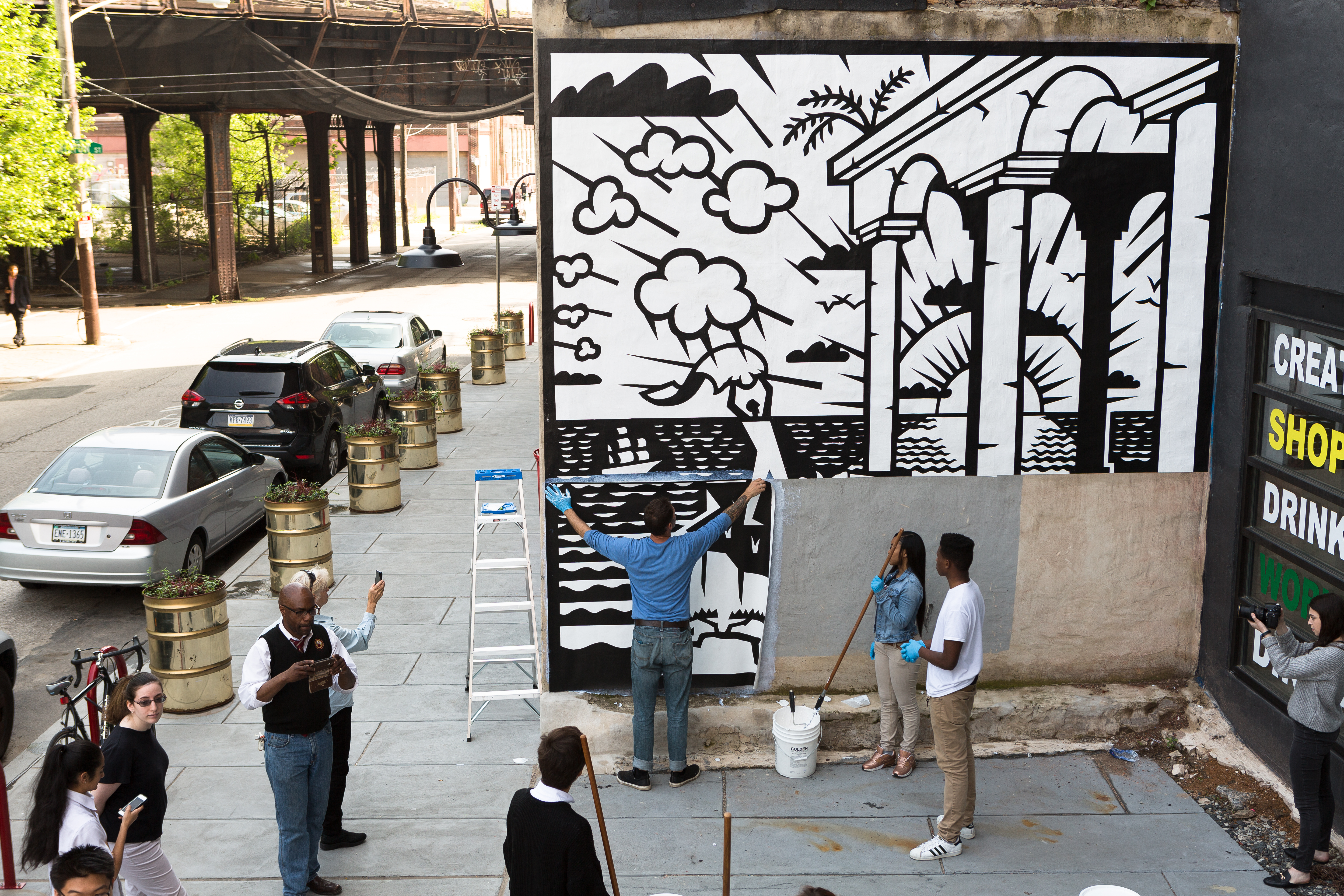 People install a panel of a large black and white mural in Philadelphia