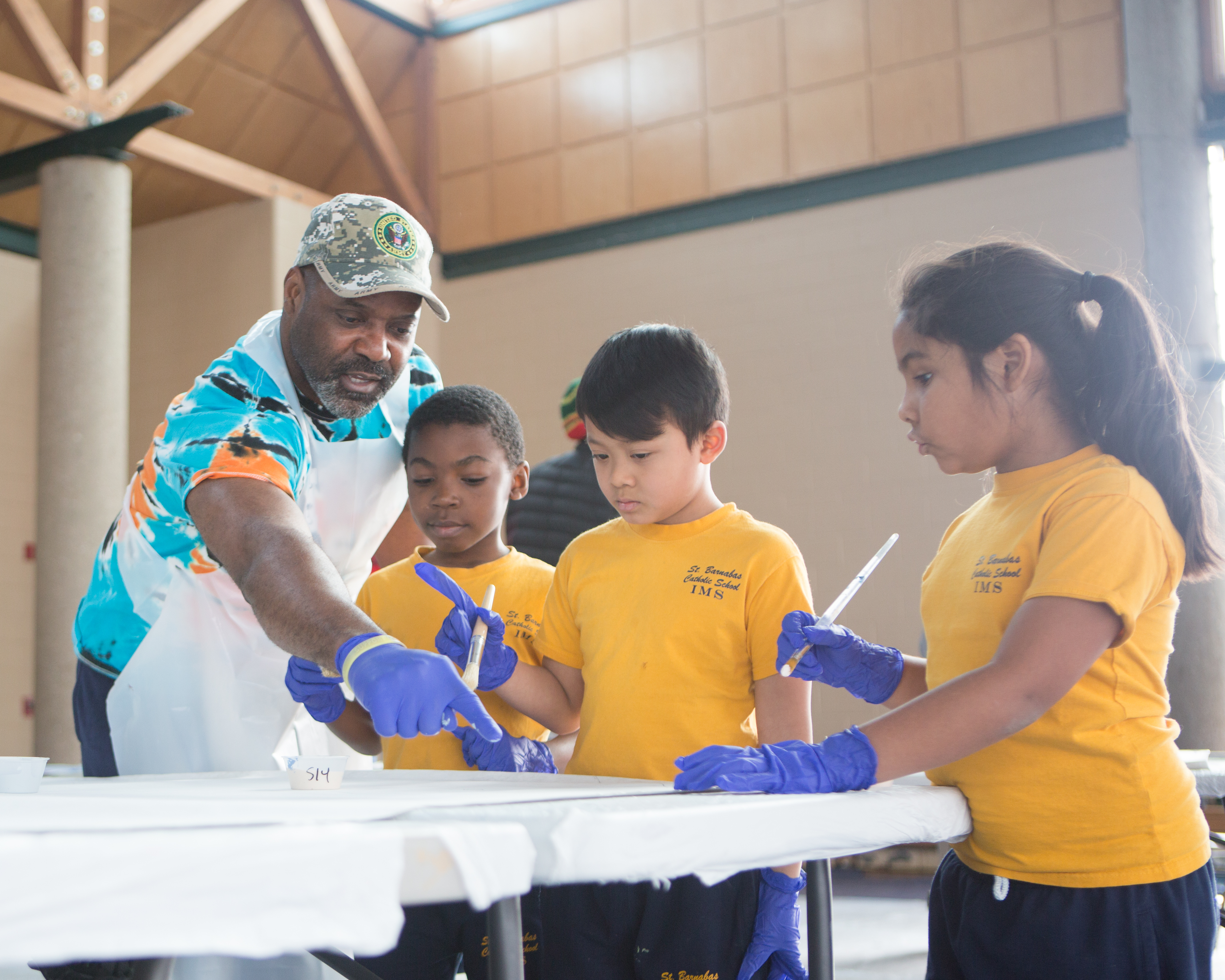 A man helps young children complete a group painting