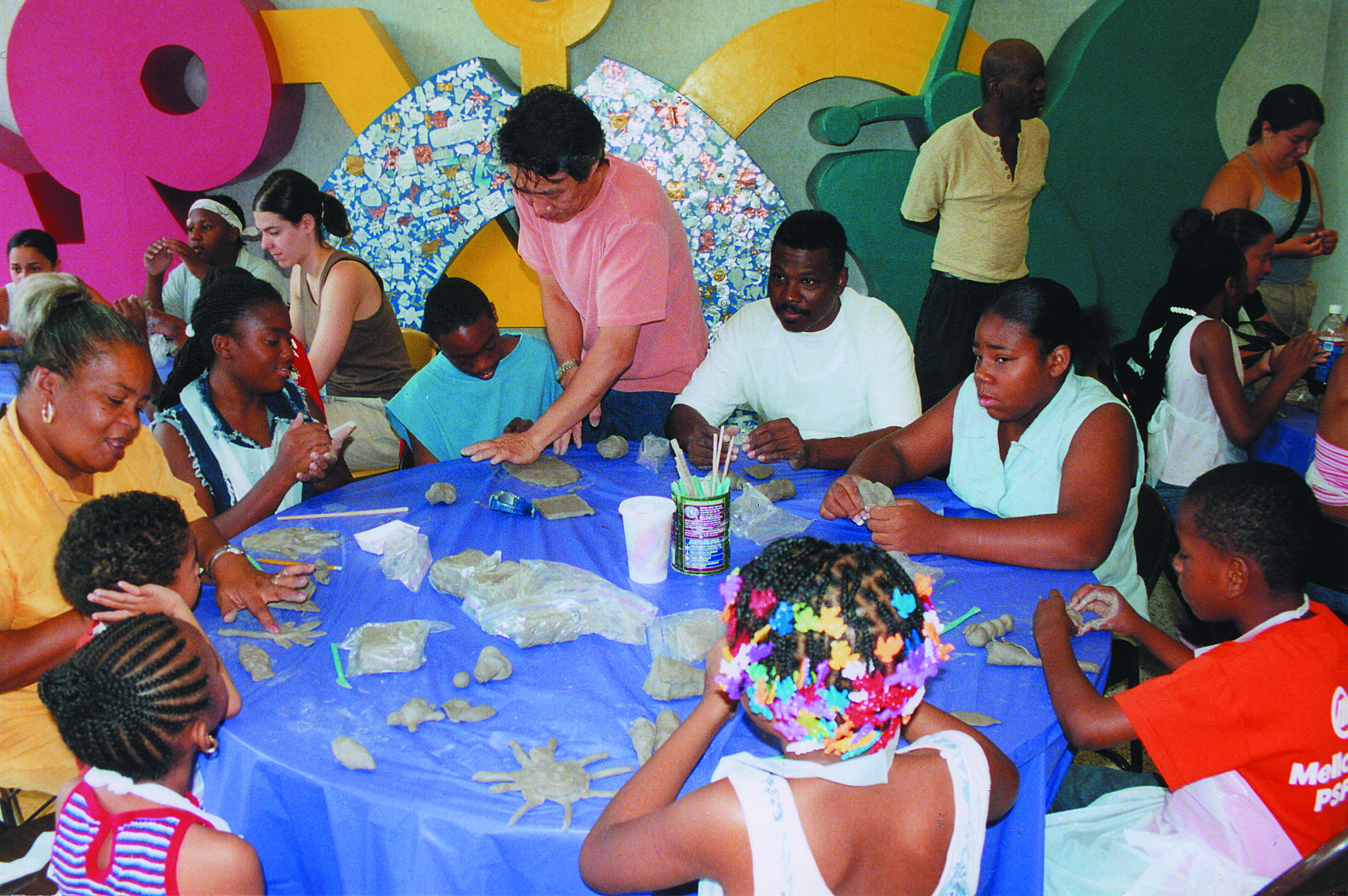 Adults and children working with clay.