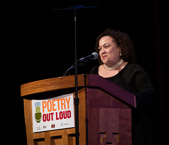 A woman speaks at a podium with a Poetry Out Loud banner hanging from it