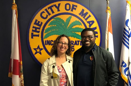 Man and woman standing in front of the City of Miami logo