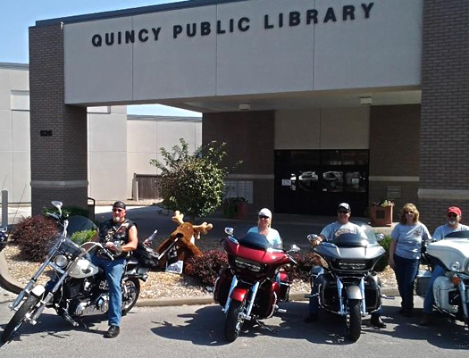 Group of adults astride their morcycles in front of the Quincy Public Library