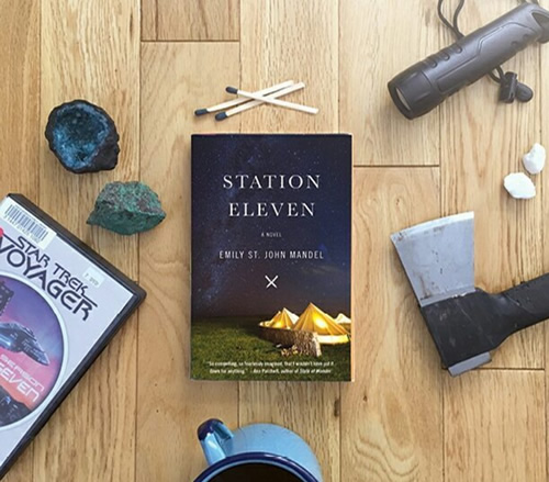 "A copy of Station Eleven, surrounded by various survival tools, a coffee mug, and a DVD copy of ""Star Trek Voyager."""