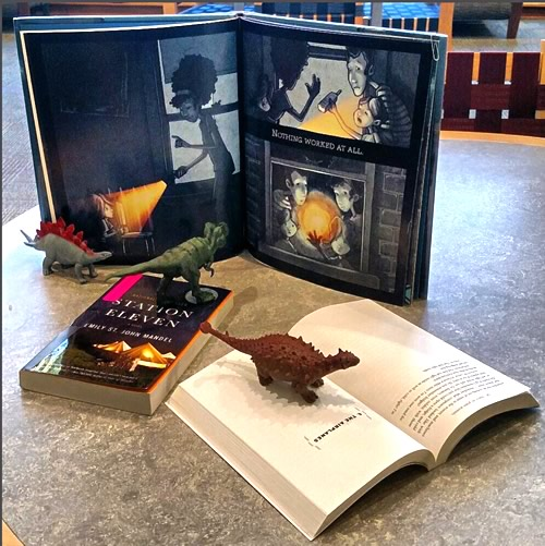 Display of Station Eleven and companion books for young readers with dinosaur figurines.