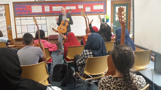 students in a classroom setting listening to a teacher who's standing in front of a board filled with music notation and terminology