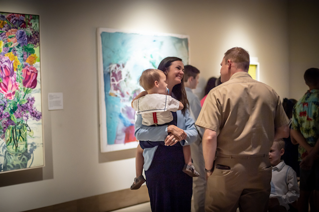 a  man and a woman holding a child talk to each other against a background of colorful paintings