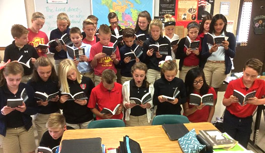 Three rows of students reading paperback copies of FIve Skies in front of the teahers desk