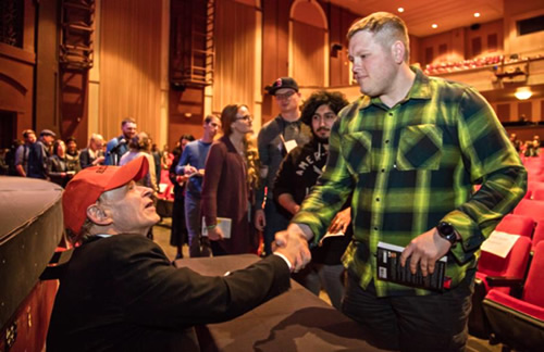 Readers lined up in auditorium with copies of The Things They Carried. Tim O'Brien shakes hand of one young man.