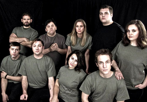 Nine students in grey shirts and stage makeup stand in front of a black backdrop