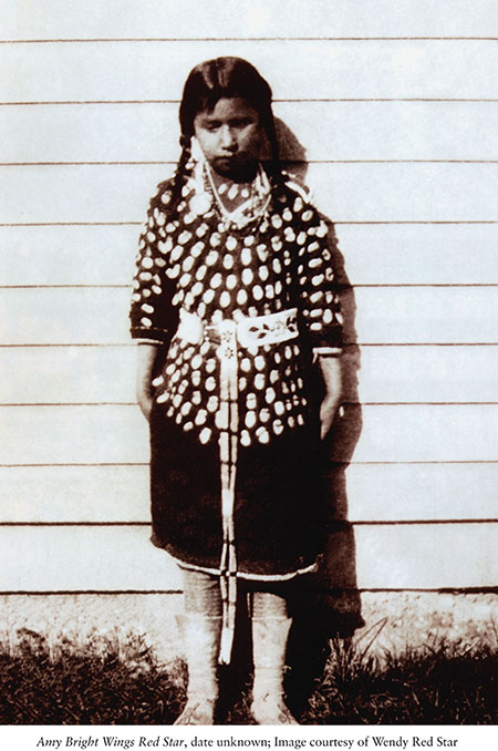 Black and white photo of a young Native girl standing in front of a wooden house.