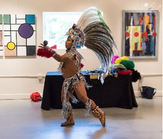 Man in Aztec garb performs a traditional dance in Arts Herndon