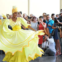 A woman in a long yellow dress and headpiece dances with people surrounding her, many taking photos.