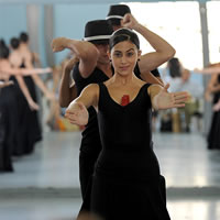 Dancers wearing black stand in three lines. One woman faces the camera holding out her hands.