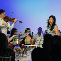 A man plays the violin next to a woman singing.