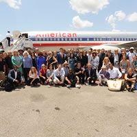 A large group of people pose in front of an airplane.
