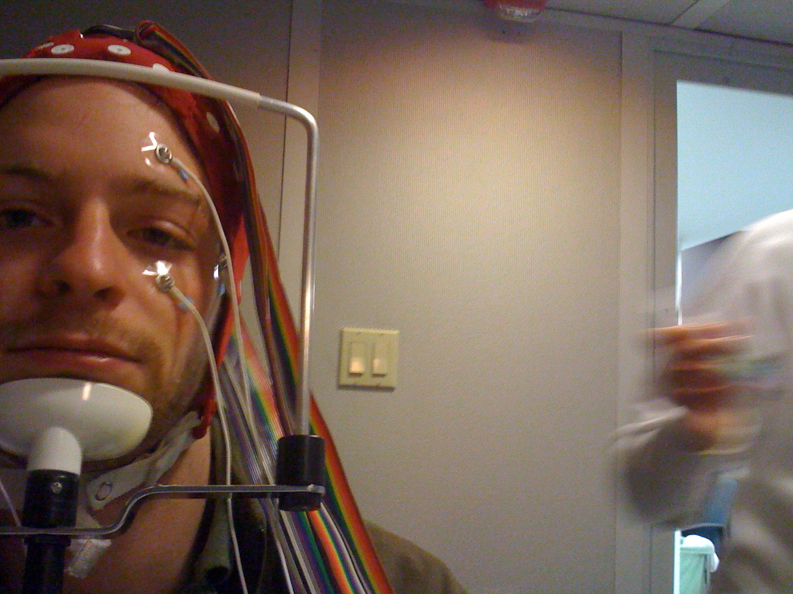 Man with wires connected to his face and head.