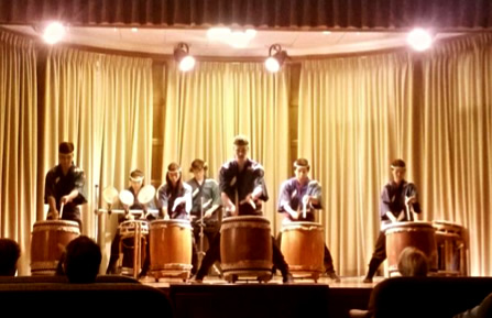 Seven taiko drummers perform on stage
