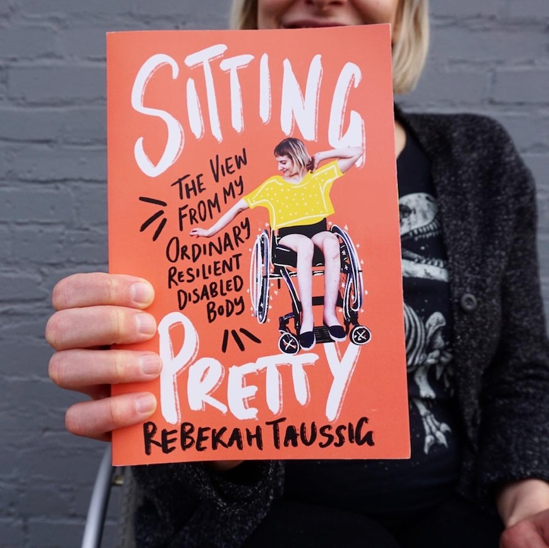 A woman holds a book cover to the camera.
