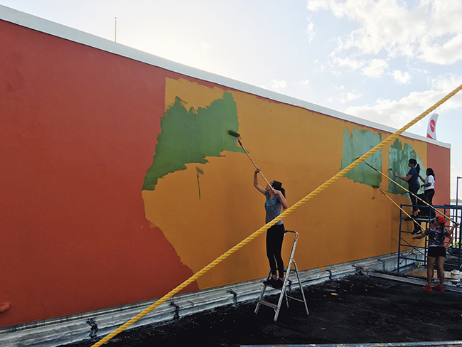 Teenage students paint an outdoor mural