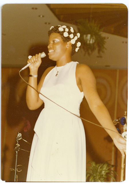 Girl in white dress with flowers in her hair singing with arm outstretched.