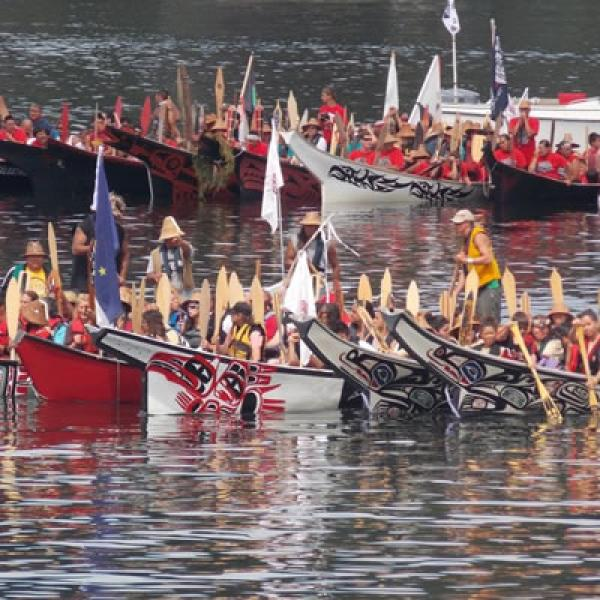 A group of canoe families conclude their journey, preparing to land on the shore of North Point in the Port of Olympia, Washington. Photo courtesy of ThurstonTalk.com