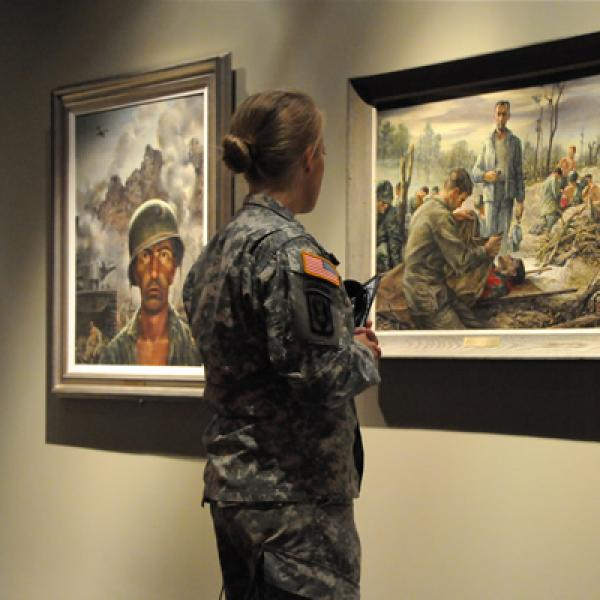 Woman in military uniform looking at art in museum.