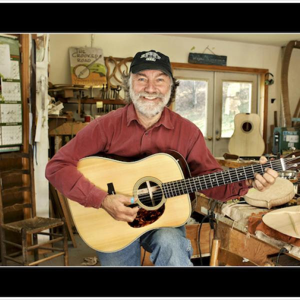 a man holding a guitar in his luthier's workshop
