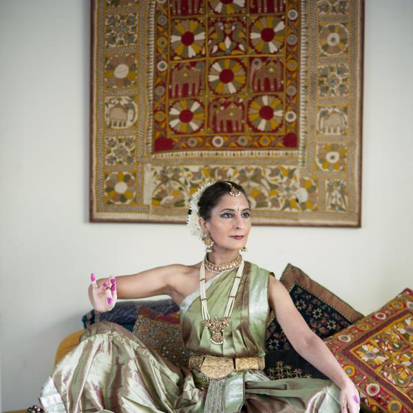 A woman in classical Indian dress seated amongst colorful pillows strikes the pose of the goddess Devi