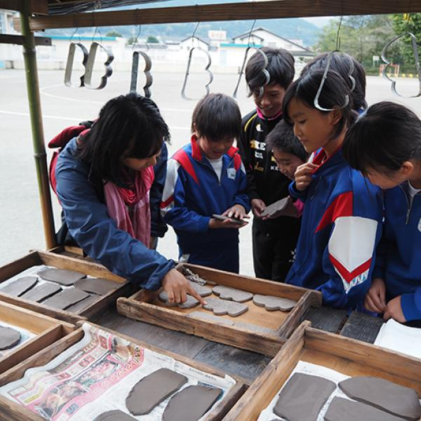 Children in Japan look inside a kiosk where clay cut-outs are laid out