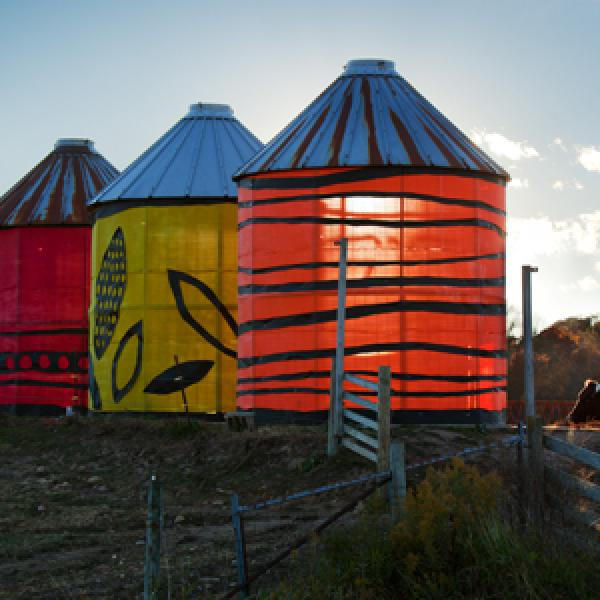 Cribs by Brenda Baker. Illuminated silo-esque structures