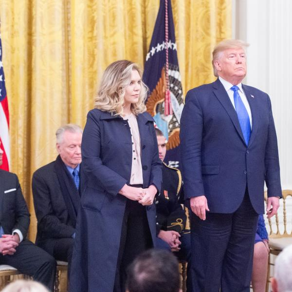 Woman in suit next to man in suit during ceremony.