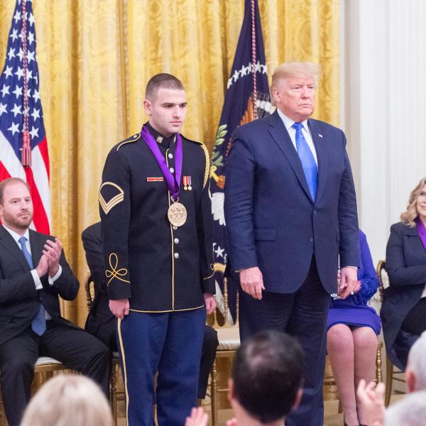 Man in uniform standing next to man in suit at ceremony.