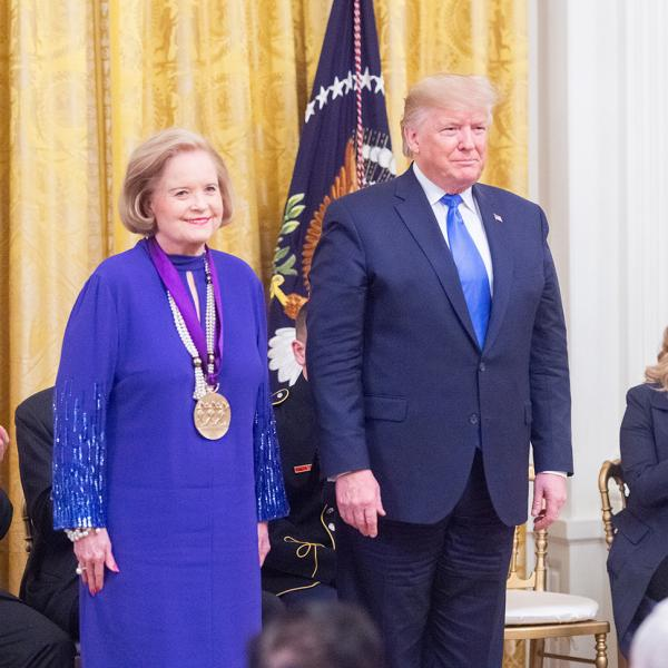 Woman in purple stands next to president.