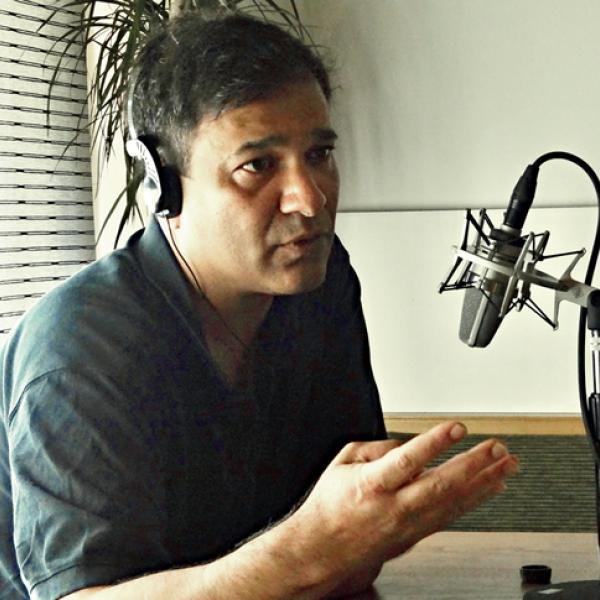 Abbas Raza with headphones and speaking into a microphone.