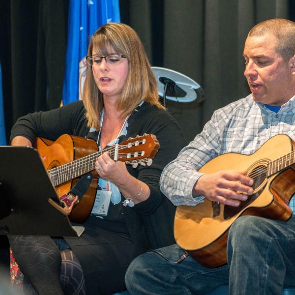 woman and man sitting down playing guitar together